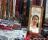 Shop keeper seen through a mirror in her shop on Silom Road, Silom, Bangkok, Thailand in March 2010