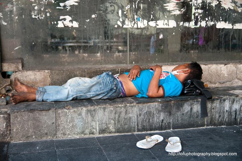 Man sleeping on Silom Road, Silom, Bangkok, Thailand in March 2010