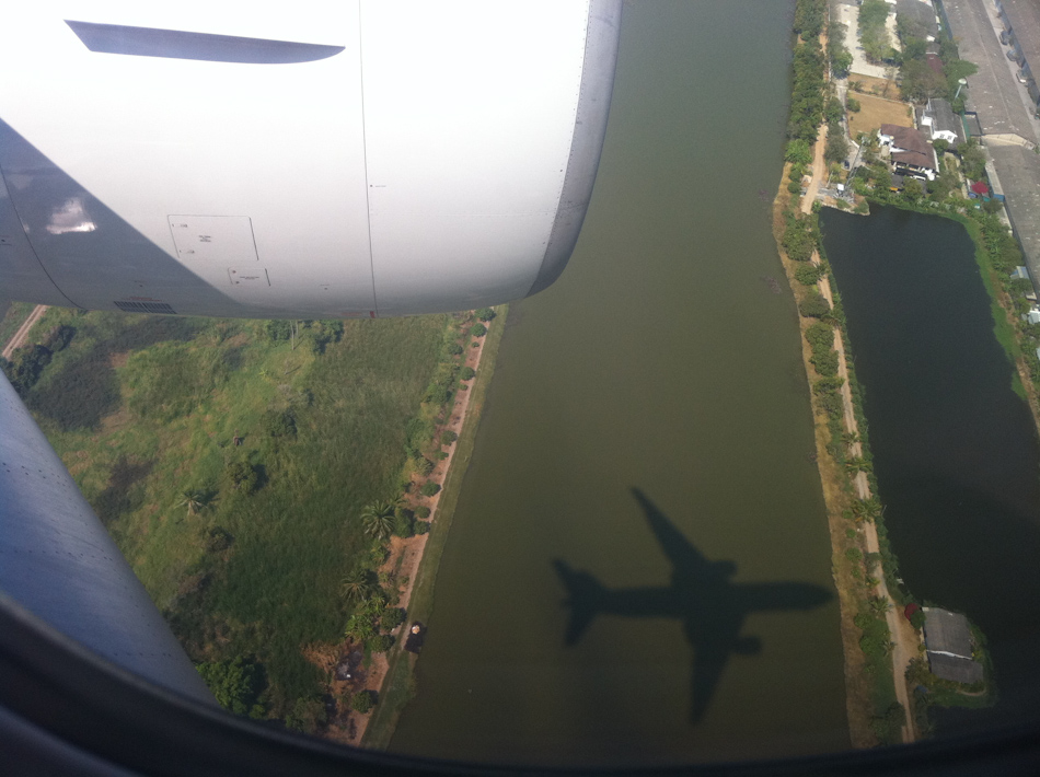 The shadow of a jumbo jet passes over the Bangkok landscape as it comes into land