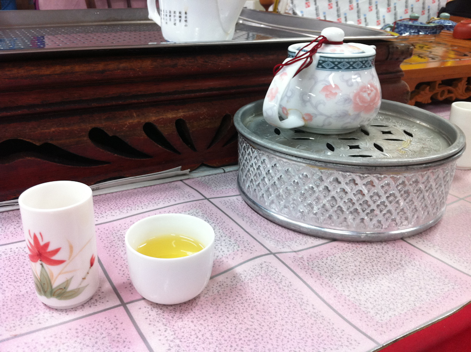 The tall cup, tea cup and the tea pot on its heater