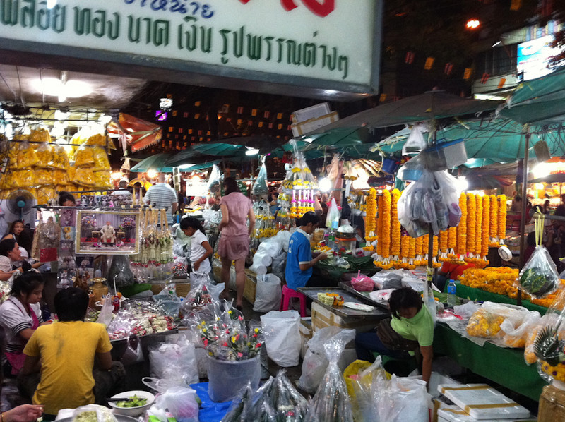The crowded vendor stalls cover the entire sidewalk at Bangkok flower market