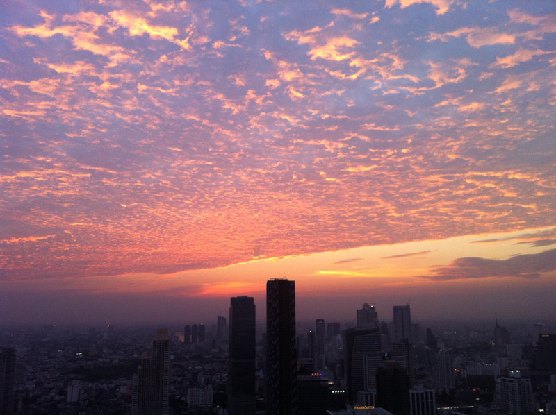As the sun slides below the horizon, it lights up the entire Bangkok sky with a fiery, dramatic red behind the clouds