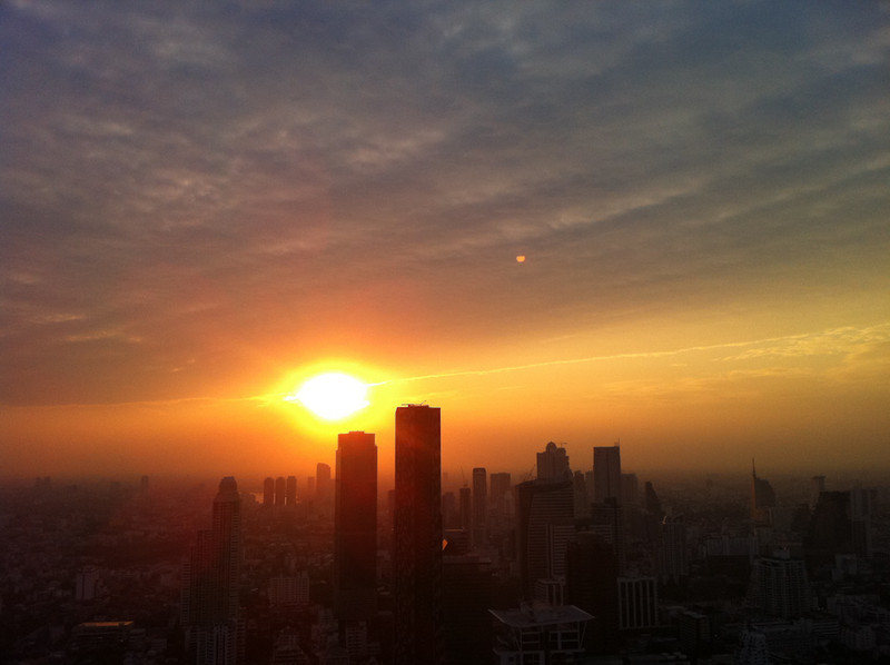 Sunset intensifies as the sun falls below Bangkok's skyscrapers