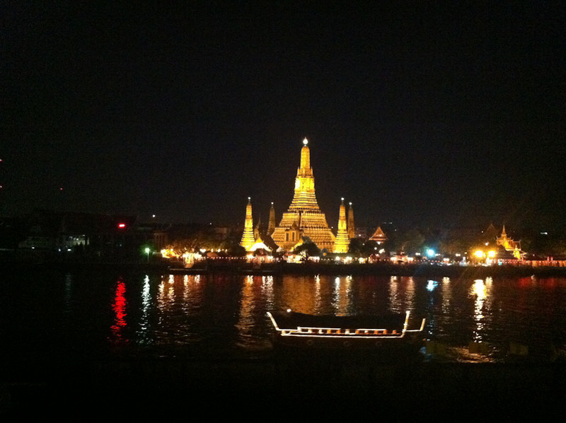 Wat Arun (the Temple of the Dawn) at night on the Chao Phraya River, Bangkok as a cruise ship passes by