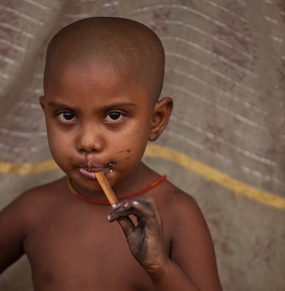 A boy living in a slum in Dhaka city. He has just finished an ice cream.