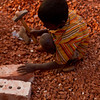 A boy at work breaking bricks.