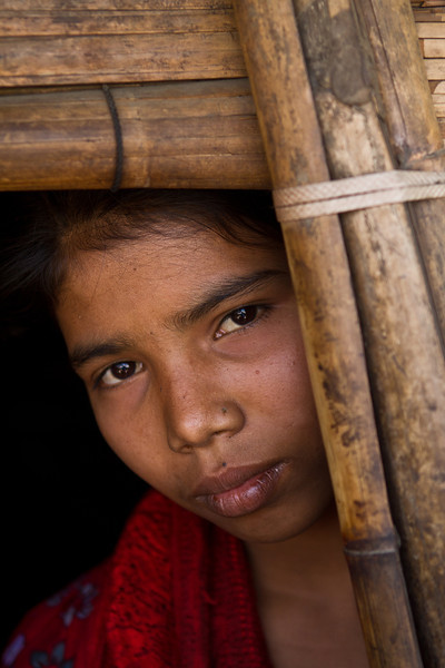 A Rohingya girl who lives in a refugee camp in Southern Bangladesh. She is born in the camp, and her parents have lived there for many years. She belongs to no country and has no rights.