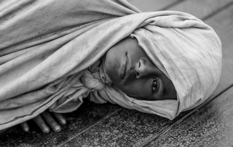 A boy who lives at the Kamalapur Railway Station in Dhaka city. It is early morning and he is just waking up