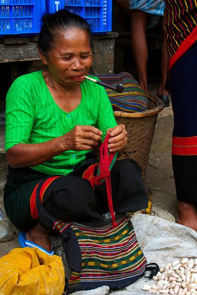Knitting and smoking at her market stall