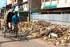A rickshaw drives past one of Chittagong's makeshift dumps