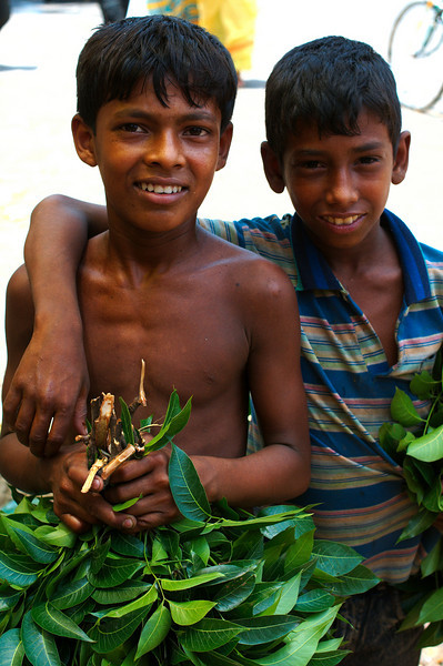 Young boys gathering up branches at the market