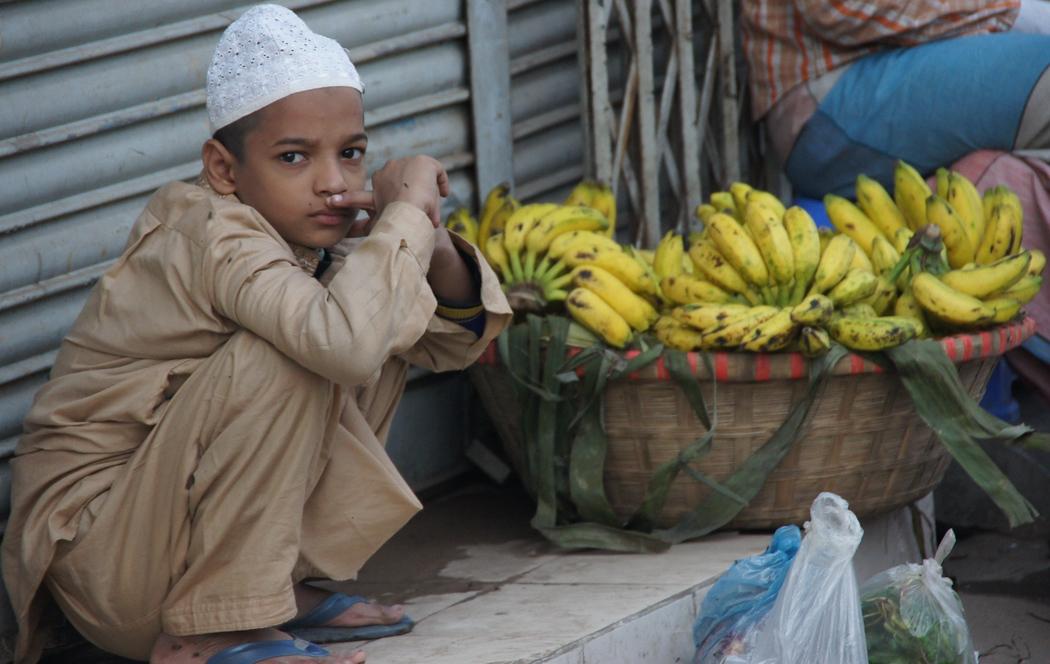 A Bangladeshi boy squats down beside bananas - Dhaka, Bangladesh.  This is a travel photo from Dhaka, Bangladesh.