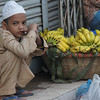 "A Bangladeshi boy squats down beside bananas - Dhaka, Bangladesh.  This is a travel photo from Dhaka, Bangladesh. <a href=""http://nomadicsamuel.com"">http://nomadicsamuel.com</a>"