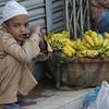 "A Bangladeshi boy squats down beside bananas - Dhaka, Bangladesh.  This is a travel photo from Dhaka, Bangladesh. <a href=""http://nomadicsamuel.com"">http://nomadicsamuel.com</a>"
