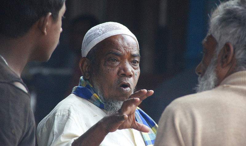 """A man with a distinct facial expression candidly interacts with others - Dhaka, Bangladesh.  Travel photo from Dhaka, Bangladesh. <a href=""""http://nomadicsamuel.com"""">http://nomadicsamuel.com</a>"""