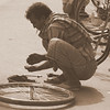 Our feature photo of the day is a shot of a Bangladeshi man bending over to repair a bicycle on the streets of Old Dhaka, Bangladesh.