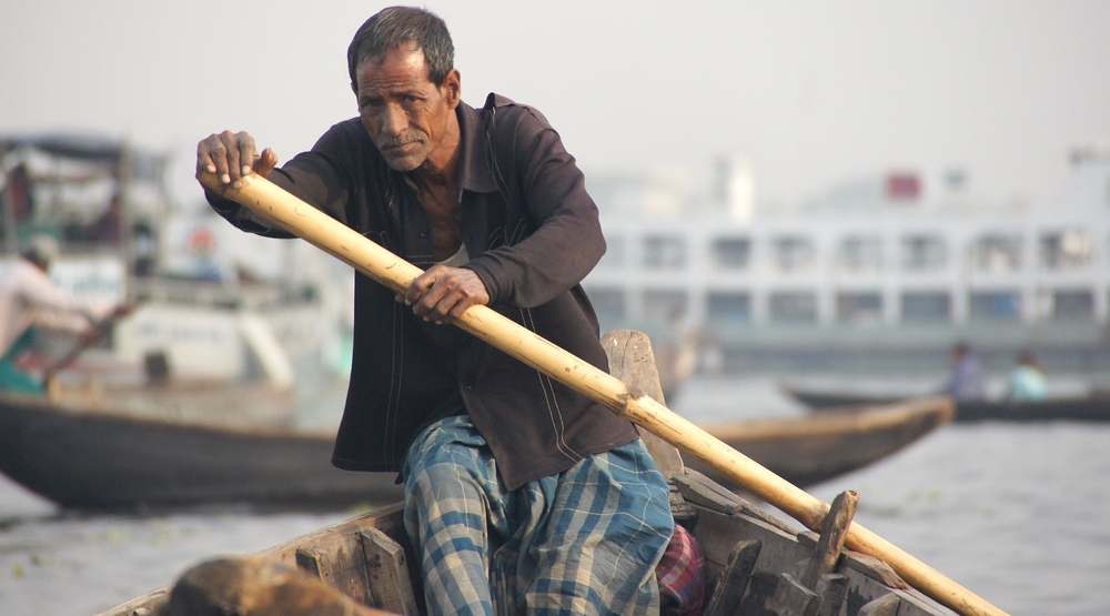 Today's daily feature travel image is of a Bangladeshi oarsman wearing traditional longyi and a charcoal colored collered shirt as he paddles along the Buriganga River in Dhaka, Bangladesh.