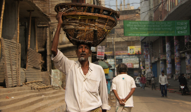 "A Bangladeshi man carrying a basket on this head - Dhaka, Bangladesh.  This is a travel photo from Dhaka, Bangladesh. <a href=""http://nomadicsamuel.com"">http://nomadicsamuel.com</a>"