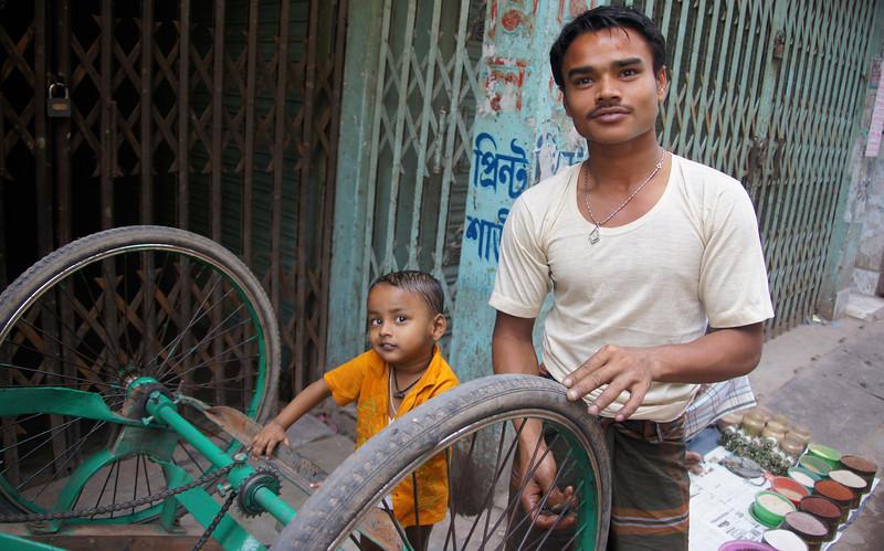 """A Bangladeshi father and his cute son repair a rickshaw wheel - Old Dhaka, Bangladesh.  This is a travel photo from Old Dhaka, Bangladesh. <a href=""""http://nomadicsamuel.com"""">http://nomadicsamuel.com</a>"""