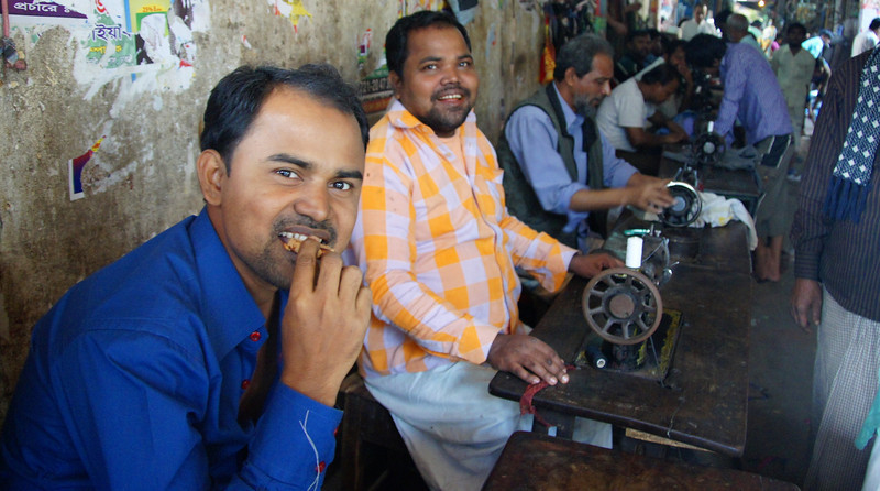 "A photo of smiling Bangladeshi men working with sewing machines - Dhaka, Bangladesh.  Travel photo from Dhaka, Bangladesh. <a href=""http://nomadicsamuel.com"">http://nomadicsamuel.com</a>"