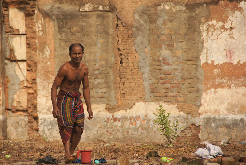 """This is a travel photo of a Bangladeshi man standing nearby a crumbling brick wall - Dhaka, Bangladesh.  Travel photo from Dhaka, Bangladesh. <a href=""""http://nomadicsamuel.com"""">http://nomadicsamuel.com</a>"""