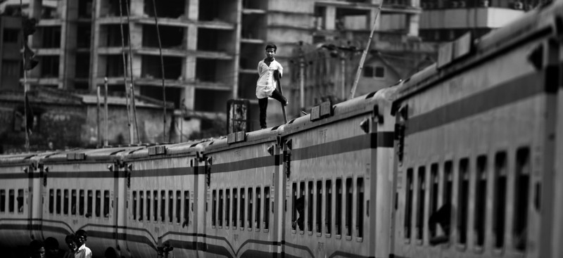 A young man going through Dhaka on top of train.
