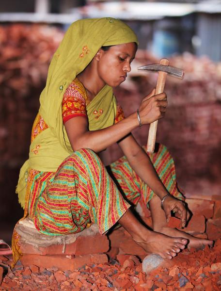 Woman breaking bricks.