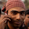 A man in a slum in Dhaka. Most people in Bangladesh have mobile phones.