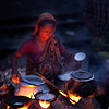 A woman early morning before sun rise, who is preparing food to sell along the track in Dhaka city.
