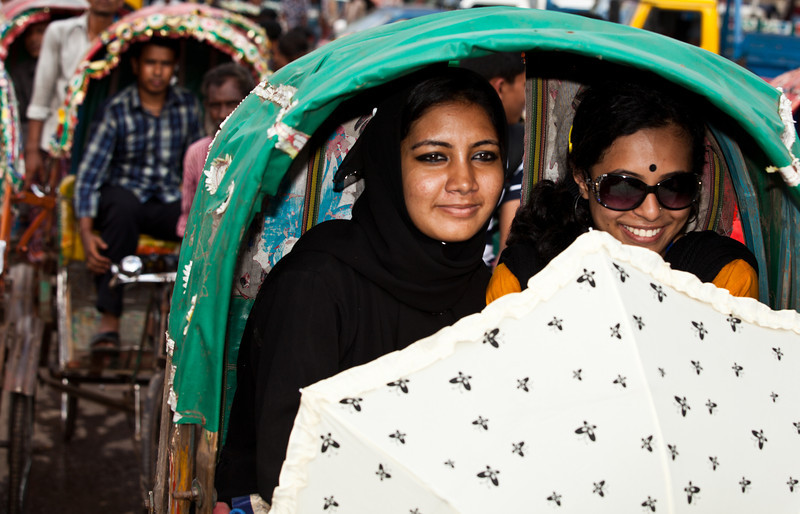 Two women waiting to pass a crossing in Dhaka mega city.