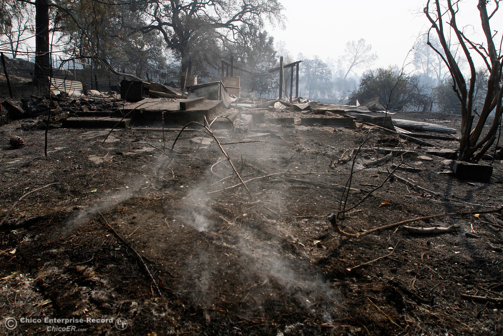 . A rug or piece of carpet smolders Tuesday, Oct. 10, 2017, outside the charred remains of the home on the 5700 block of La Porte Road in Bangor, California, after the La Porte Fire ripped through the unincorporated Butte County community Sunday night. (Dan Reidel -- Mercury-Register)