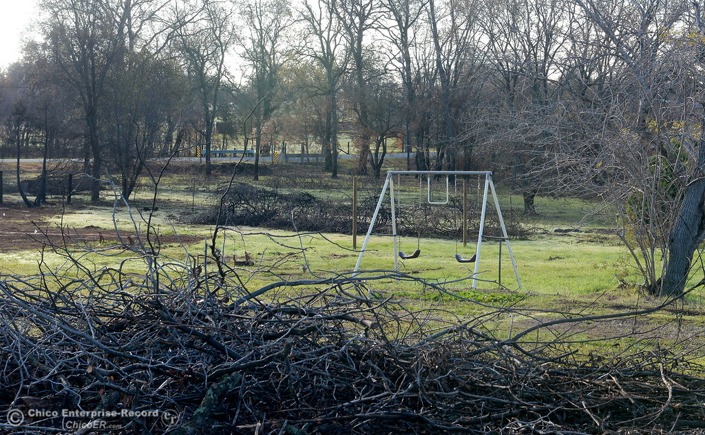 . A swingset is seen in a green field surrounded by brush piles as state and federal agencies help clean up debris following the La Porte Fire in Bangor, Calif. Wed. Dec. 13, 2017. (Bill Husa -- Enterprise-Record)