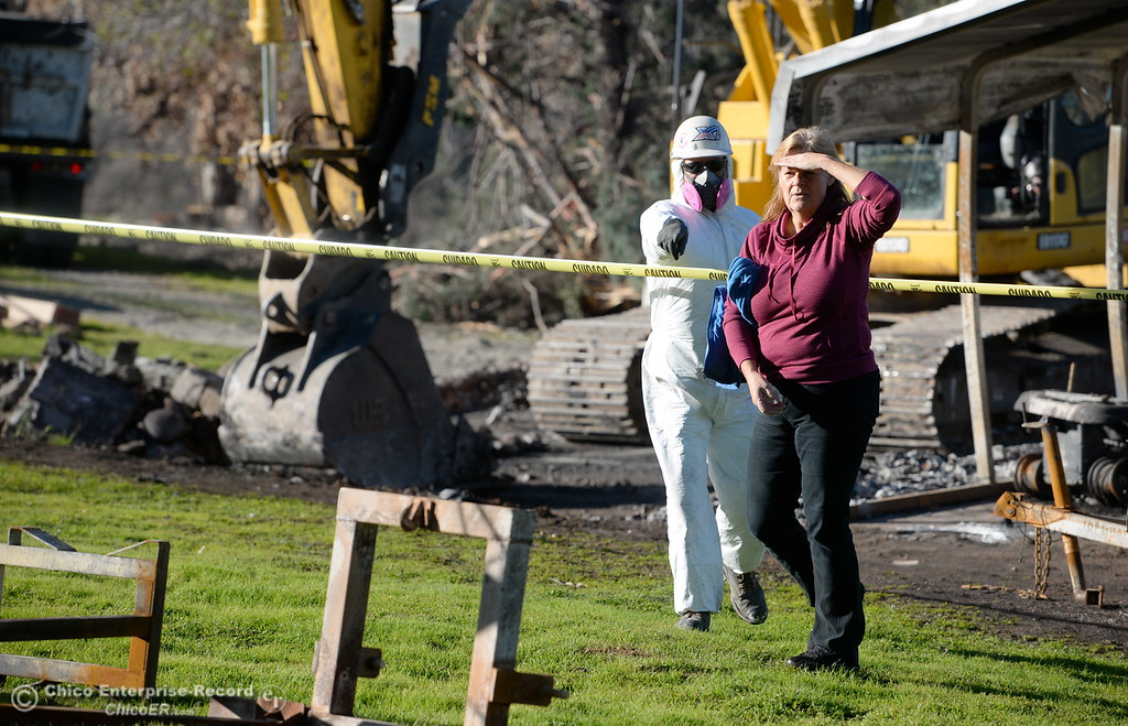 . Bangor Ranch and Vinyard Owner Karen Papillon looks for salvagable items as State and Federal agencies help clean up debris at the Bangor Ranch and Vinyard following the La Porte Fire in Bangor, Calif. Wed. Dec. 13, 2017. (Bill Husa -- Enterprise-Record)