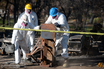 Dressed in protective equipment, Scott Feri, Ramon Villareal and Henry Villareal left to right work to move a heavy metal item as State and Federal agencies help clean up debris at the Bangor Ranch and Vinyard following the La Porte Fire in Bangor, Calif. Wed. Dec. 13, 2017. (Bill Husa -- Enterprise-Record)