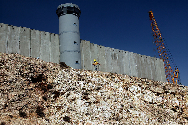Palestinian construction workers build the separation wall - Kalandia checkpoint, August 2005.