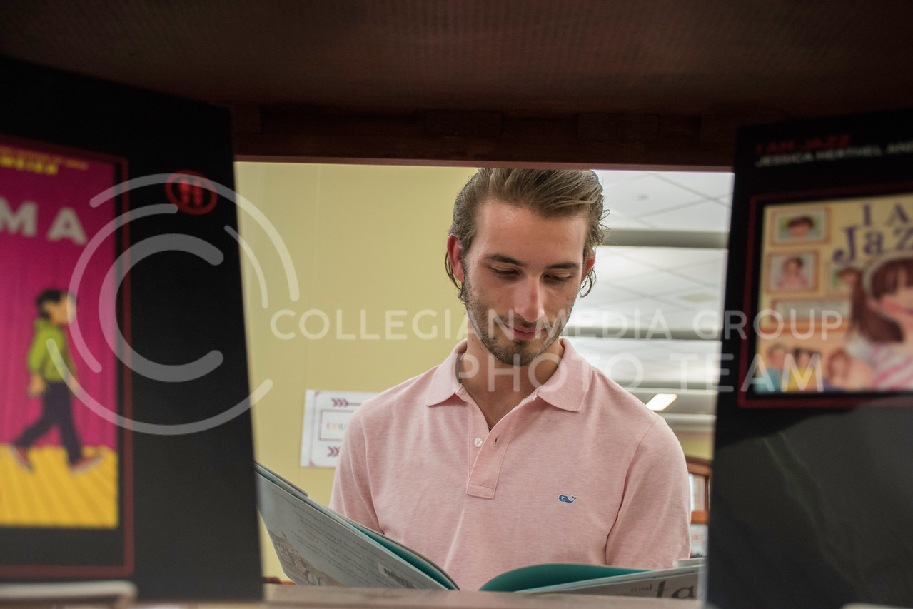 """Andrew Breen, a sophomore studying Finance at Kansas State, reads one of the """"Banned Books"""" at the Banned Books Exhibit on Sept. 28, 2017. (Olivia Bergmeier 