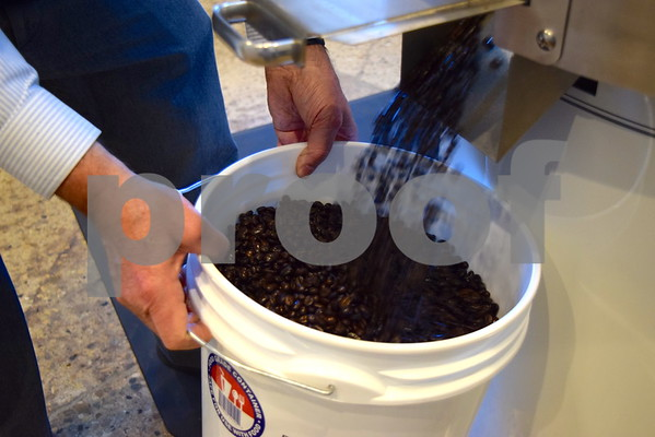 Jack Cress collects coffee beans in a container after they are roasted. Cress will use the roasted coffee beans to create a blend of specialty coffee for Barb City Roasters.