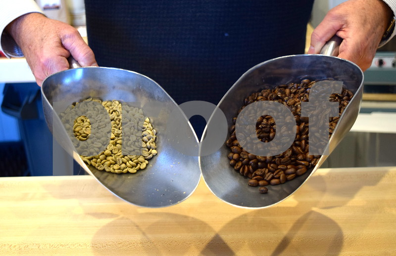Jack Cress, who creates his own specialty coffee, holds unroasted (left) and roasted Indonesian Java beans. Cress roasts coffee beans and creates his own blends for his coffee business, Barb City Roasters.