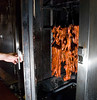 The marinated pork loin strips are skewered and hung in the oven to roast for about 50 minutes. When done they are dunked in a molasses based sauce. Some ovens use charcoal, but most use gas. The burners go around the bottom of this well-insulated cabinet.