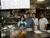 """Sun Wah BBQ has been an Uptown Chicago destination since 1987 and in January 2018 it was named an American Classic by The James Beard Foundation. Sun Wah, which means New China, is very much a family venture. Founder and owner Eric Cheng is second from the left. To his left is his niece, Carol Mak, and to his right is his eldest daughter Kelly, and third child, Michael. Not show in Mr. Cheng's wife Lynda, and his youngest child, Laura, a culinary school graduate. Another sister, Cindy, is not involved in the restaurant, but her infant daughter is already a foodie. At age one, she won't eat anything that isn't flavorful.<br /> <br /> Eric Cheng learned Chinese barbecue, in Guangdong Province in Southern China, home of Cantonese cuisine. He fled Mao Zedong's Cultural Revolution in China in 1972 by swimming eight hours to Hong Kong where he apprenticed and became a Barbecue Master. He met his wife Lynda in Hong Kong, and they married and moved to New York in 1976. There he worked for a restaurant and before long he opened the first Sun Wah on Mulberry St. in 1983. He quickly tired of the pace and people in NY and moved to Chicago in 1986.<br /> <br /> Kelly, Laura, and Mike are taking on more and more responsibility as their father plans his retirement. """"He thinks he will travel a lot"""" Kelly chuckles. """"We don't think so."""" Kelly is taking over much of the management, including a move to a new, larger location a few blocks away in summer 2009. Among the changes they are planning a prix fix menu. Laura, works in the kitchen, focusing on modernizing the menu. Mike also works in the kitchen. The family also own Sun Hing Food, a manufacturer of tofu, soy milk, and bean sprouts, which they use in Sun Wah.<br /> <br /> Located at 5039 N. Broadway, Chicago, IL. Phone  773-769-1254."""