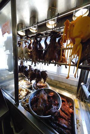 Ducks, chickens, and and cuttlefish hang in a case in the store's window above strips of barbecue pork.