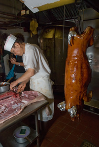 "On the left, a cook ties wires around the bones in the hip so the pig can be hung in the oven, and on the right is a roasted Philippino style pig a few minutes after being removed from the oven. The ears and tail are covered with foil to prevent charring.  Philippino Pig is marinated inside the cavity with a sauce heavy in garlic and pepper, and it has a glossy skin.  Hong Kong Pig has a salty fermented soy bean paste paste marinade with 5 spice powder, garlic and a hint of sweetness. The skin of raw Hong Kong pig is scalded with hot water and then dried overnight. When it cooks at high heat, the moisture creates ""sesame skin"", a pebbly dimpled texture. Both preparations create wonderfully crisp cracklins."