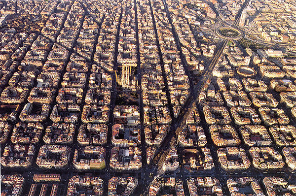 Aerial view of the L'Eixample district in Barcelona, with the spires of the Sagrada clearly visible above the other buildings. <i>From a postcard by TRIANGLE POSTALS</i><br> 380.3 Barcelona. Vista aèria, © Pere Vivas
