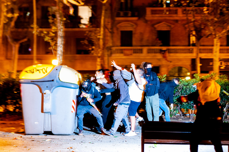 Barcelona, Spain - 18 october 2019: young catalans throw bottles and stones at police during riots for catalonia independence at night causing riots in the city center