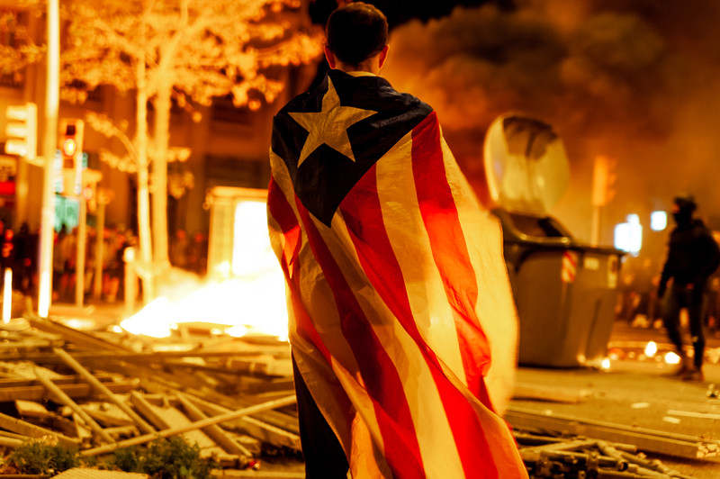 Barcelona, Spain - 18 october 2019: catalan activist with catalan flag at night with fire and destruction in background during clashes with police