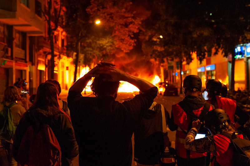 Barcelona, Spain - 16 october 2019: a neighborhood watches in despair while buildings and cars burn at night during city riots between police and pro independence activists