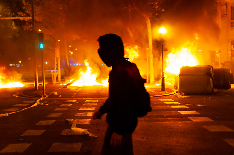 Barcelona, Spain - 16 october 2019: a young catalan protester walk against huge fire in the background during riots with police expressing anger and power