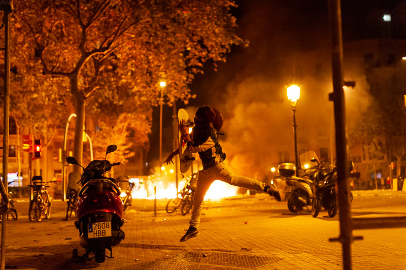 Barcelona, Spain - 18 october 2019: young masked catalan throw bottles and stones at police during riots for catalonia independence at night causing riots in the city center