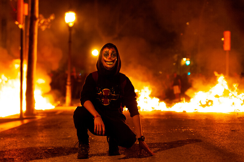 Barcelona, Spain - 18 october 2019: catalan protest with joker mask stand in front of fire during riots with mossos police at night with creepy atmosphere