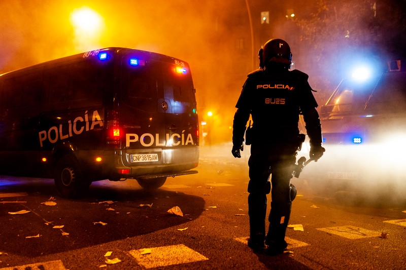 Barcelona, Spain - 18 october 2019: mossos d'esquadra amid fog and smoke catalan police with guns confront with protesters at night during clashes with young activists with fire in background